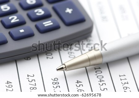 Close-up of silver pen and calculator on paper table numbers.