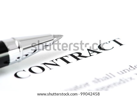 Close-up of silver pen on contract. Selective focus on top of pen.