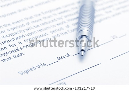 Close-up of silver pen on employment agreement. Selective focus on top of pen. Toned image.