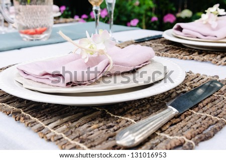 Close up of simple rustic outdoor entertaining table setting with neutral nude colour scheme