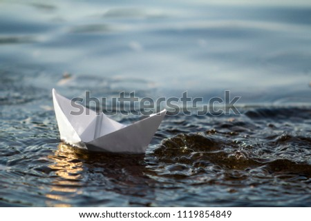 Close-up of simple small white origami paper boat floating in blue clear river or sea water under bright summer sky. Beauty of nature, freedom, dreams and fantasies concept.