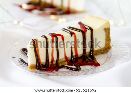 Close up of single slices of cheesecake on display with chocolate and strawberry sauce drizzled on top