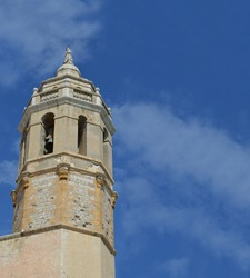 Close up of Sixteenth Century Steeple of San Bartolomé and Santa Tecla Baroque-style church that overlooks the Balearic Sea in Stiges Spain