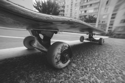 Close up of skateboard on the city road. Extreme sport challenge and skateboarder training, urban lifestyle, black-and-white picture