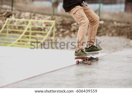 Close-up of skateboarders foot while skating in skate park #606439559