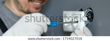 Close-up of skillful handyman installing socket. Man using screwdriver, electrician professional caring for electricity. Specialist fixing plug, mounting outlet Photo stock ©