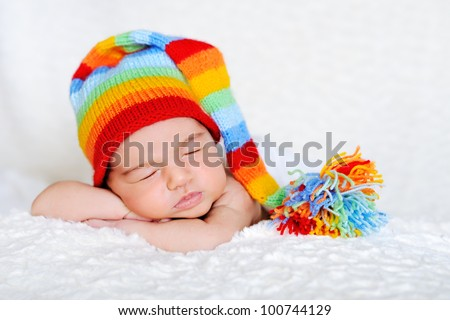 Close-up of sleeping newborn posed on white blanked, wearing colorful stocking cap