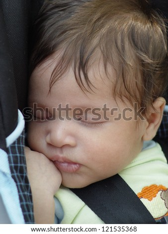 Close Up of Sleeping Two Month Old Infant Baby with car seat strap