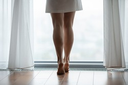 Close up of slender legs of young beautiful female dressed in short bathrobe standing barefoot on toes on warm heated wooden floor at large panoramic window of modern flat hotel suite meeting new day
