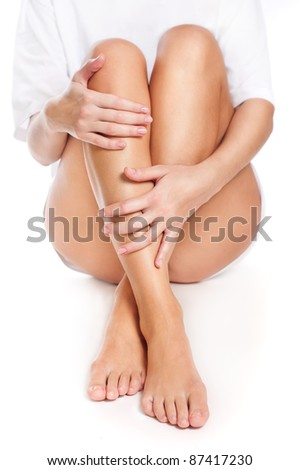 Close up of slender naked legs being massaged isolated on white - healthcare and beauty concept - stock photo