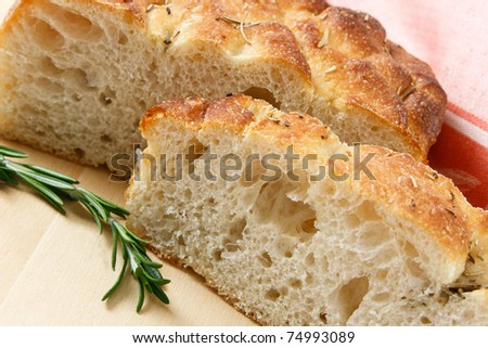 Close up of sliced artisan focaccia bread with a sprig of rosemary