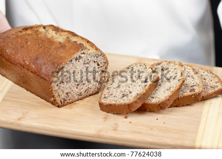 Close-up of sliced banana bread with a chef standing in the background.
