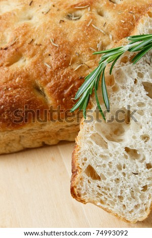 Close up of sliced rosemary focaccia with a sprig of rosemary