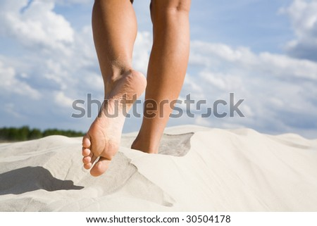 Close-up of slim legs of female walking down sandy beach with cloudy sky at background