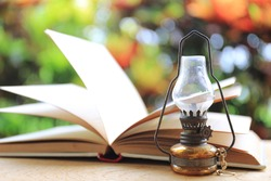 Close-up of small antique lamps Open old books and colorful light from nature as the background selective focus and shallow depth of field