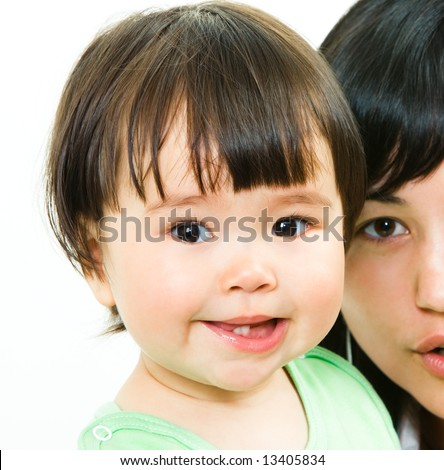 Close-up of small girl's face looking at camera with her mother on the background