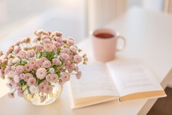 Close-up of small pink flowers bouquet in glass vase with blurred soft focused background of pink cup of tea or coffee and opened book by the window. Slow living concept.
