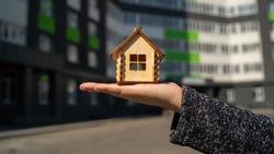 Close up of small wooden house in woman's hand on background of built house. Concept of purchasing new apartment.