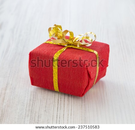 Close up of small wrapped gift box Small red gift box decoratively packed into red paper and tied around with golden ribbon