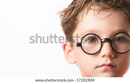 Close-up of smart guy in preschool age looking at camera through glasses