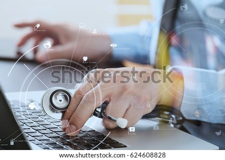 close up of smart medical doctor working with laptop computer and stethoscope on dark wooden desk with virtual reality icon diagram