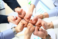Close-up of smart people performing cooperation gesture to greet presumptive boss or colleagues and show increased level of cohesion and solidarity. Company meeting concept
