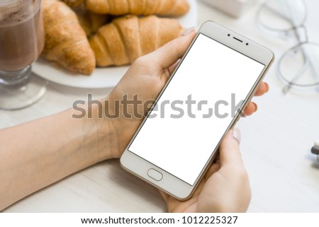Close up of smart phone in girl`s hands In a cafe on the background of a wooden white table #1012225327