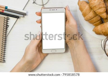 Close up of smart phone in girl`s hands In a cafe on the background of a wooden white table #795818578