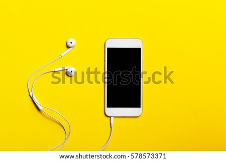Close-up of smart phone with headphones on a yellow background. (Top view). Listen to music.