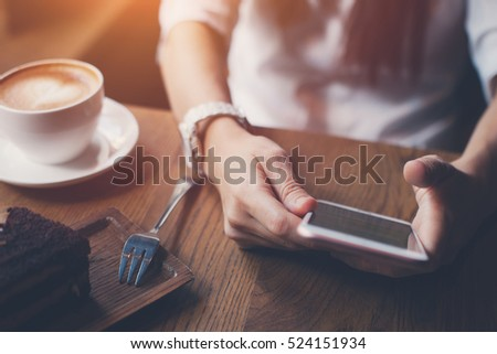 Close-up of smartphone in woman's hands typing message, sitting in cafe with cup of coffee and cake #524151934