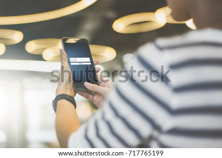 Close-up of smartphone with inscriptions on screen - user name, password, log in. Foreground and background in soft focus. Online marketing, education, e-learning, e-commercial, social media, network. #717765199