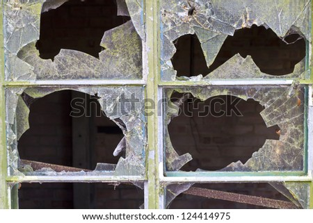 Close up of smashed reinforced panes of glass in a window in a delapidated building