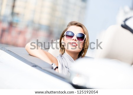 Close up of smiley woman in the cabriolet wearing cute sunglasses