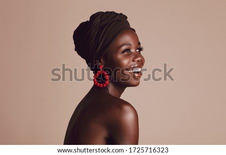 Close up of smiling african woman on beige background. Beautiful female model with a cloth wrapped on head looking away and smiling. Stockfoto ©