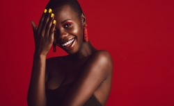 Close up of smiling african woman wearing vivid makeup against red background. Female model with buzz cut hairstyle looking at camera and smiling.