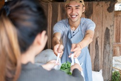 Close up of smiling Asian man holding plastic bags filled with vegetables as they are handed out to consumer at a vegetable stall