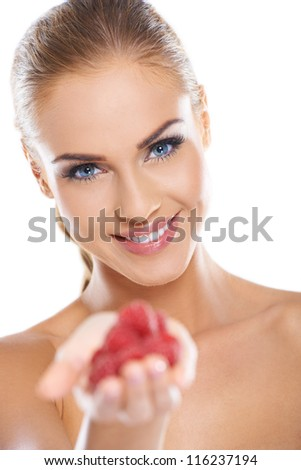 Close up of smiling blonde holding raspberries while isolated