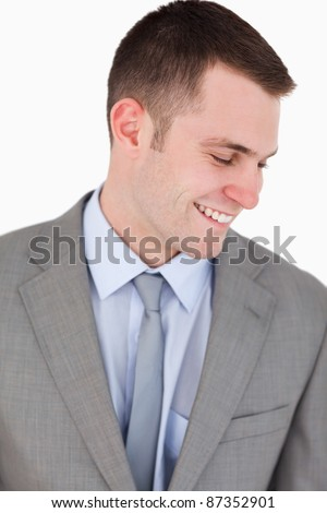 Close up of smiling businessman looking down on white background