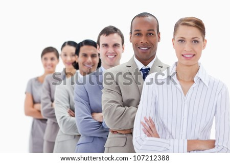 Close-up of smiling colleagues dressed in suits crossing their arms in a single line with focus on the first man
