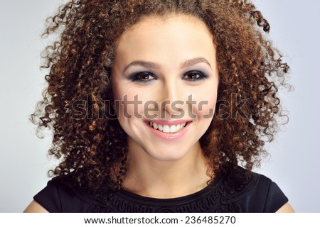 Close up of smiling curly hair woman  - Shutterstock ID 236485270