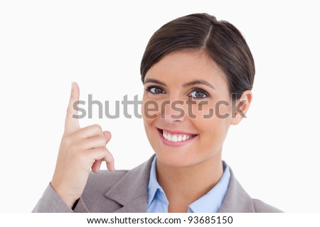 Close up of smiling female entrepreneur pointing up against a white background