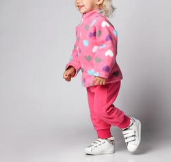 Close-up of smiling happy blonde baby kid girl in pink warm fleece clothing jacket  with hearts print pattern and pants running, having fun. Happy childhood and trendy children wear concept