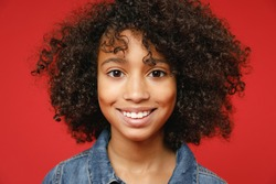 Close up of smiling little african american kid girl 12-13 years old wearing casual denim jacket looking camera isolated on red color background children studio portrait. Childhood lifestyle concept