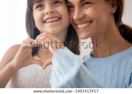 Close up of smiling mom and preschooler daughter hug showing heart sign with hands, happy young mother and little cute girl child make love gesture express affection and care. Parenthood concept