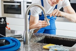 Close-up of smiling plumber fixing a faucet with blue pipes on the countertop