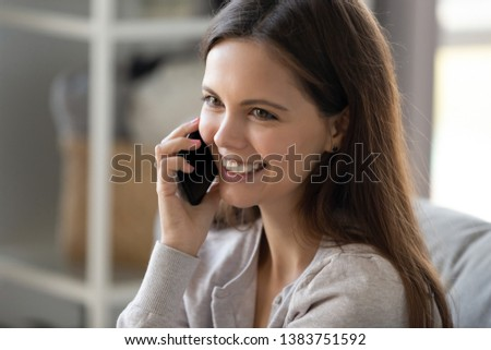 Close up of smiling positive teen girl talk on smartphone having pleasant conversation with friend, happy young woman hold cellphone speaking communicating use wireless or 5g connection