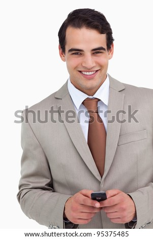 Close up of smiling salesman holding his cellphone against a white background