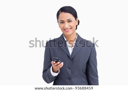 Close up of smiling saleswoman holding cellphone against a white background