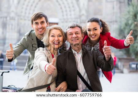 Close up of smiling tourists posing on European city street #607759766