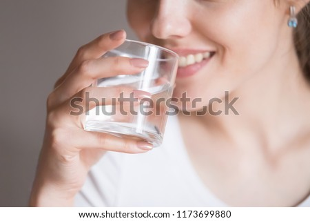 Close up of smiling woman feeling thirsty enjoying pure mineral water, dehydrated young female holding glass drinking aqua, girl taking care of own health. Concept of healthy lifestyle, good habit